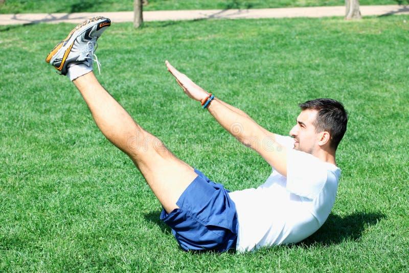 L'esercitazione dell'uomo di forma fisica si siede su fuori in erba di estate MA adatto fotografia stock