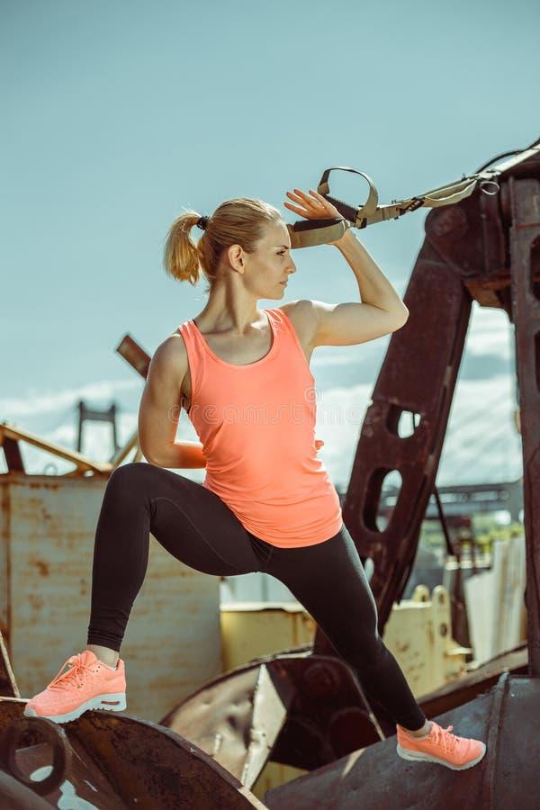 L'esercitazione muscolare dell'atleta femminile inserisce su fuori il giorno soleggiato fotografie stock