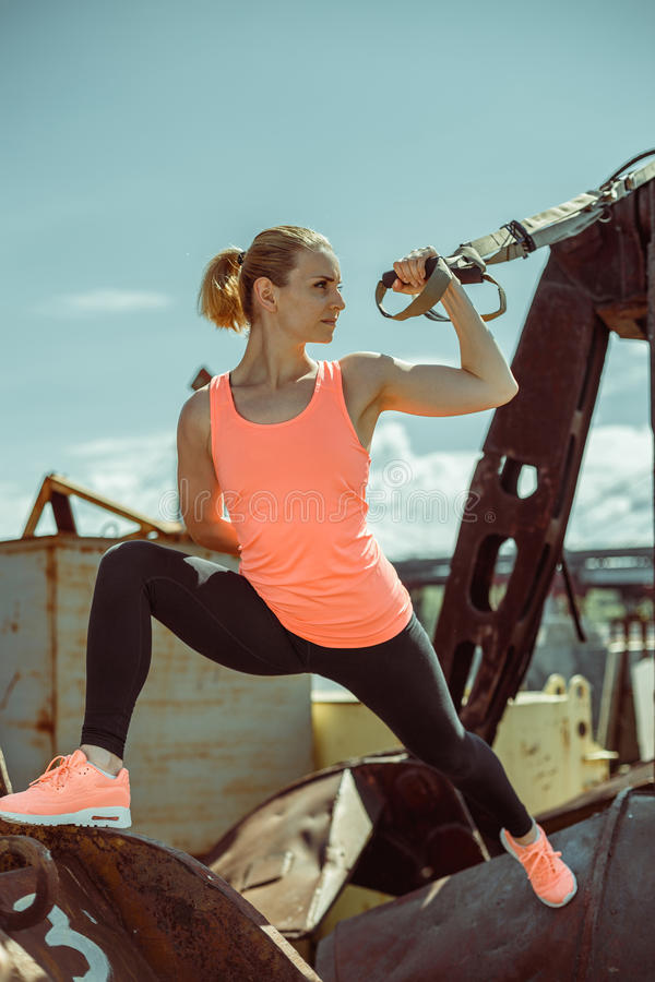 L'esercitazione muscolare dell'atleta femminile inserisce su fuori il giorno soleggiato fotografie stock libere da diritti