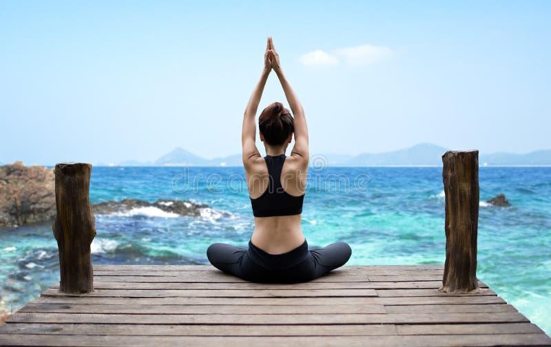 L'esercitazione sana di stile di vita della donna vitale medita e yoga di pratica alla spiaggia, fondo della natura fotografia stock