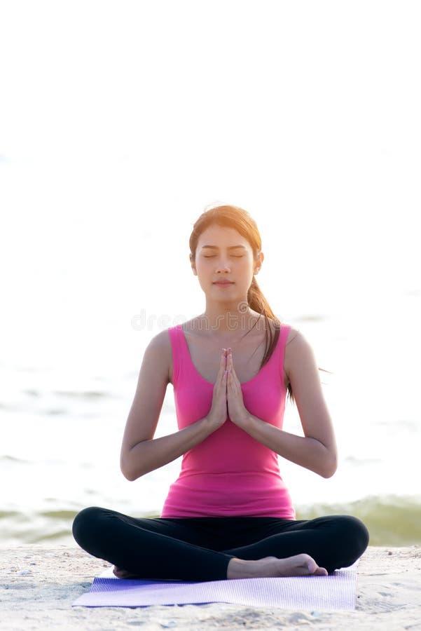 L'esercitazione sana di stile di vita della giovane donna vitale medita e yoga di pratica alla spiaggia, fondo della natura immagini stock libere da diritti
