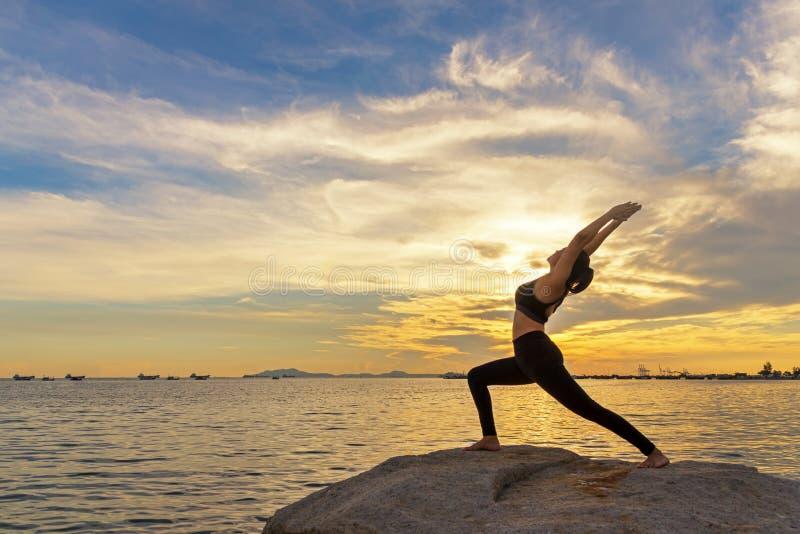 L'esercitazione sana di stile di vita della donna della siluetta vitale medita e yoga di pratica all'aperto su roccia al tramonto fotografia stock libera da diritti
