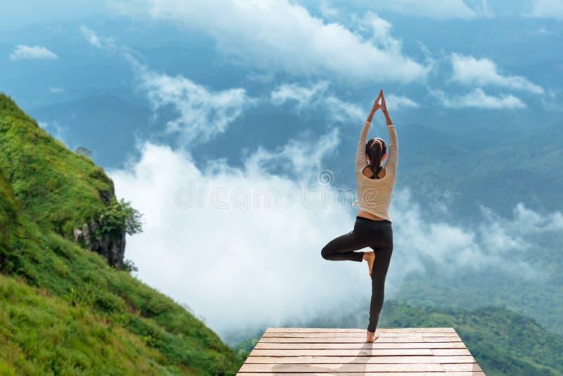 L'esercitazione sana di stile di vita della donna vitale medita e yoga di pratica al ponte nella mattina la montagna, immagini stock libere da diritti