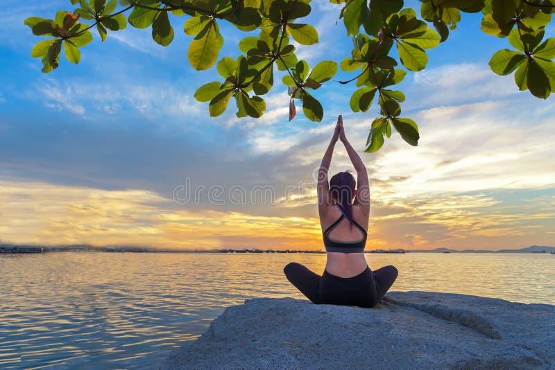 L'esercitazione sana di stile di vita della donna di yoga vitale meditano e l'yoga su roccia vicino alla spiaggia, il tramonto di immagine stock libera da diritti