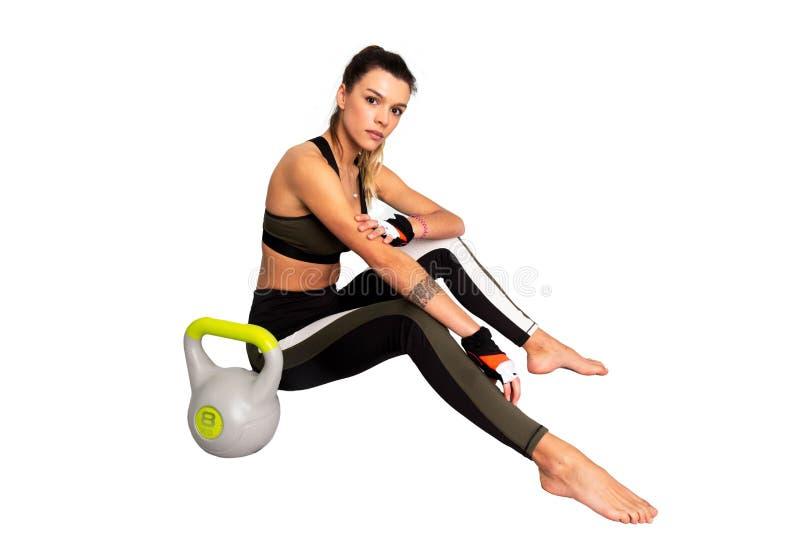L'esercizio della donna, rottura di forma fisica si rilassa dopo l'allenamento del kettlebell o la seduta stanca, resto che prepa immagini stock libere da diritti