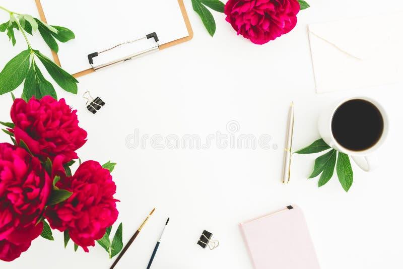 L'espace de copie de Blogger ou d'indépendant avec le presse-papiers, le carnet, les fleurs de pivoine et la tasse de café sur le photo stock