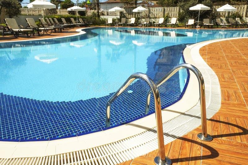 L'espace piscine de natation du nouveau complexe résidentiel de luxe avec des tuiles, des poignées d'escaliers de chrome et des d photo libre de droits