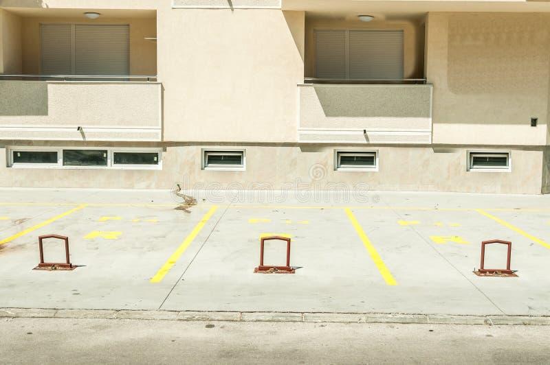 L'espace privé de parking pour des voitures avec la réservation numérote devant le bâtiment résidentiel dans le lo de barrières d images stock