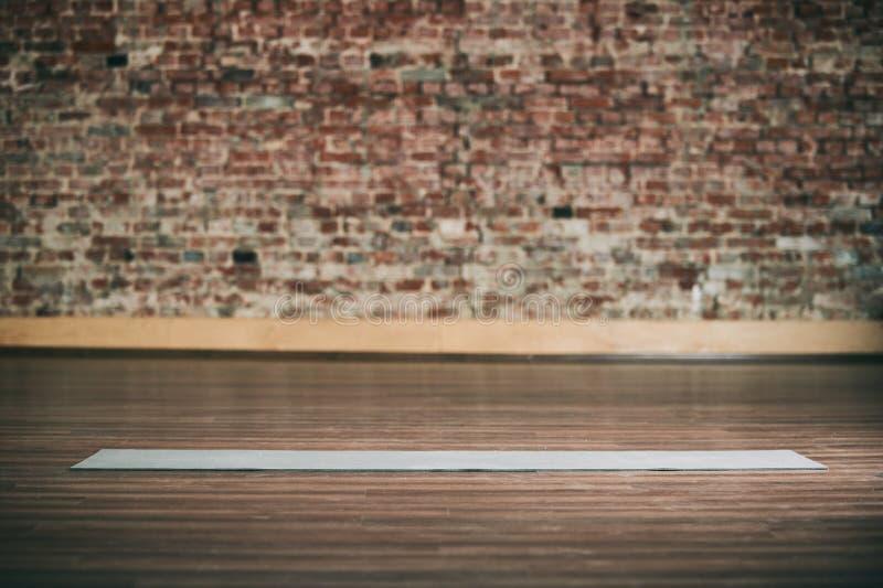L'espace vide au centre de fitness, mur de briques, plancher en bois naturel, studio moderne de grenier, tapis déroulé de yoga su photo stock