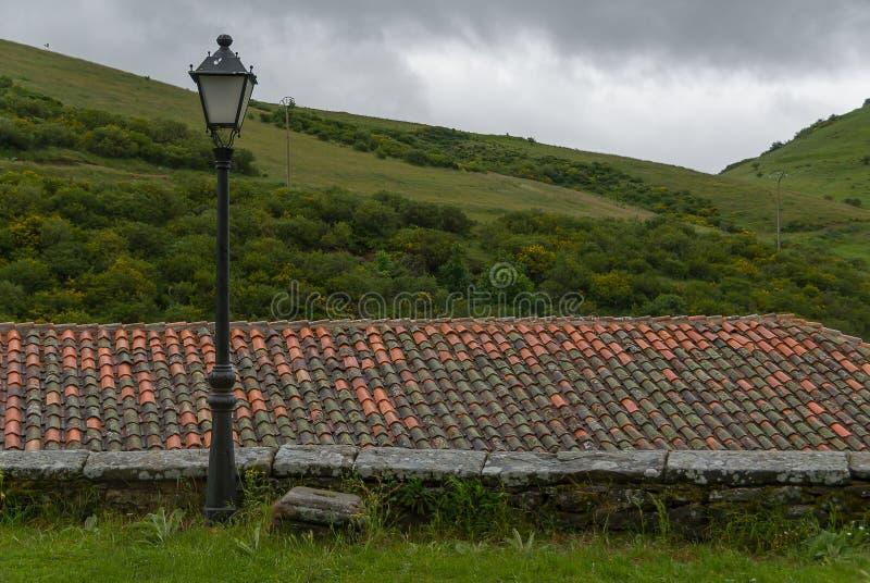 l'espagne Lampadaire, dessus de toit sur le fond vert de montagne de palentina photos libres de droits
