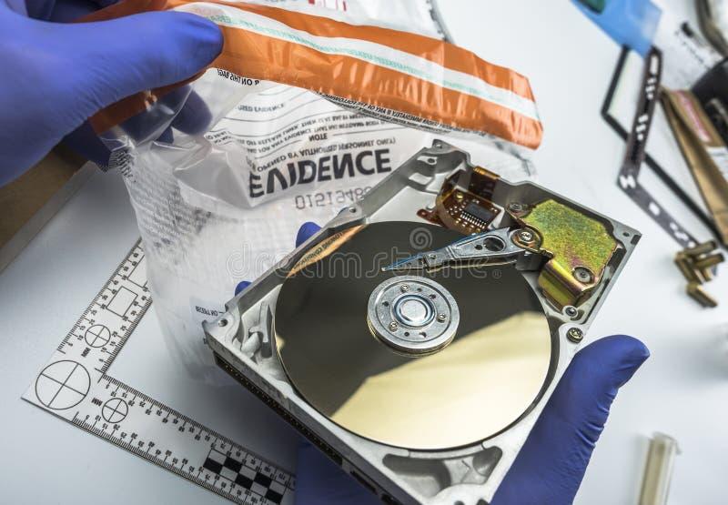 L'esperto nella polizia esamina il disco rigido alla ricerca di prova immagini stock libere da diritti