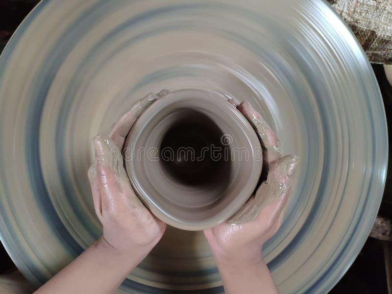 L'esperto sta scolpendo l'argilla nella forma desiderata È uno del processo di fabbricazione delle terraglie fotografia stock libera da diritti