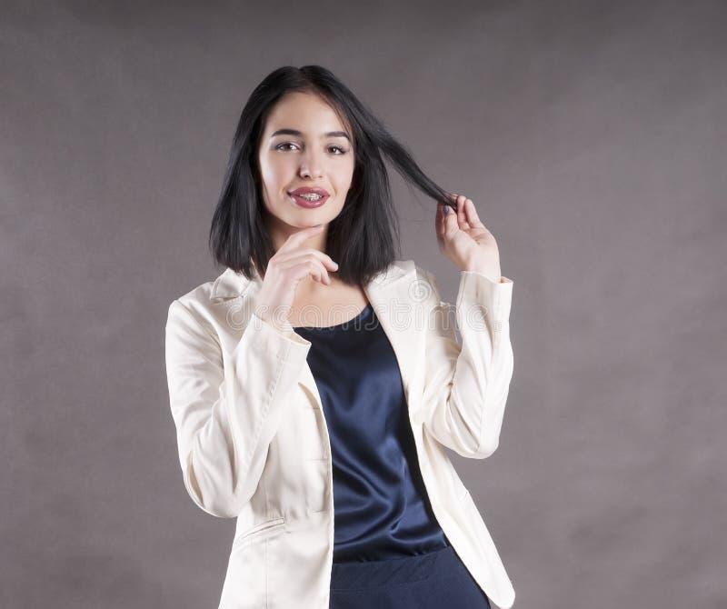 L'espressione allegra della positività della giovane bella eleganza felice della donna di affari rinforza lo studio castana fotografia stock