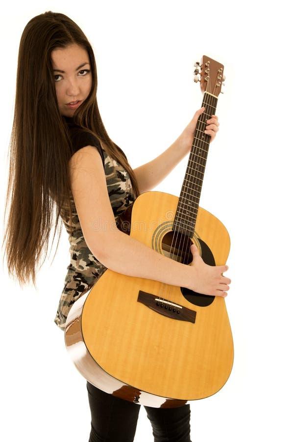 L'espressione allegra sui modelli femminili affronta il gioco della sua chitarra immagine stock libera da diritti