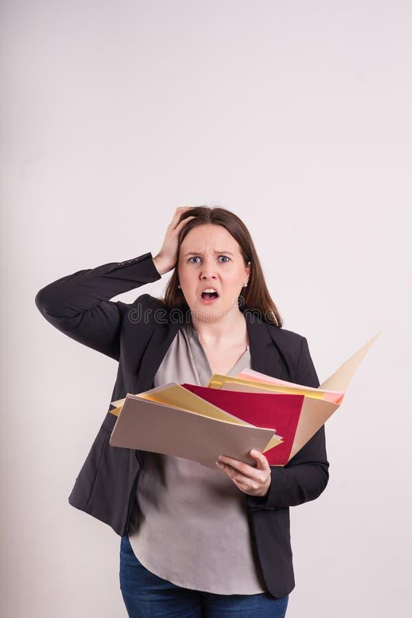 L'espressione della frustrazione sulle giovani donne affronta la tenuta le carte e delle cartelle di archivio sparse su fondo sol immagine stock
