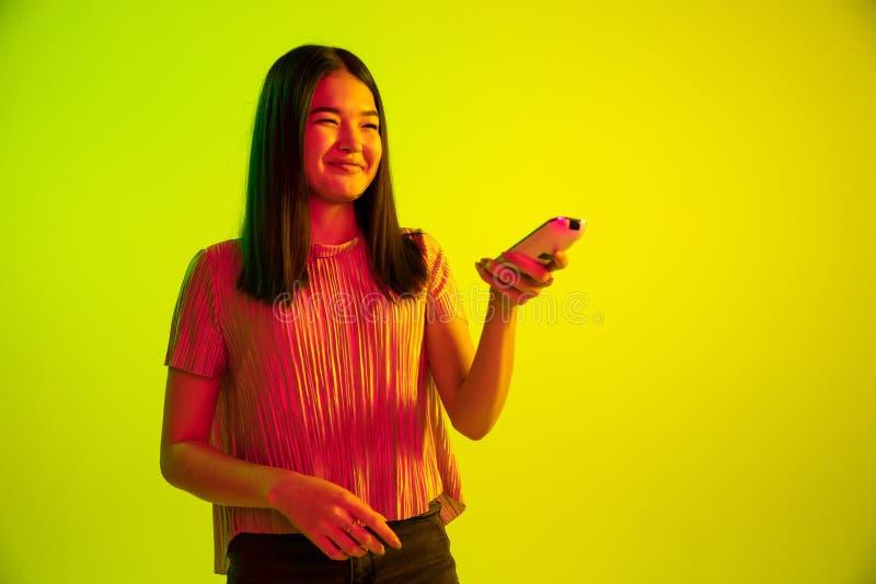 L'espressione facciale della bella ragazza alla luce al neon sul fondo giallo dello studio fotografia stock libera da diritti