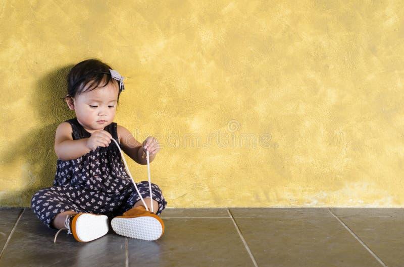 L'essai asiatique mignon d'enfant en bas âge à l'attachement/portent ses propres chaussures brunes photos stock