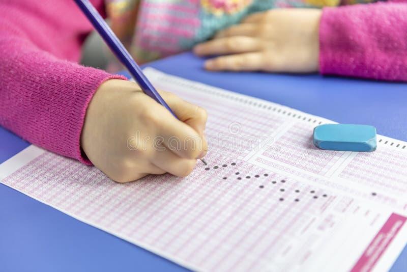 L'essai d'étudiant de main dans l'exercice et la prise complètent la feuille d'ordinateur de papier carbone d'examen de crayon à  photo libre de droits