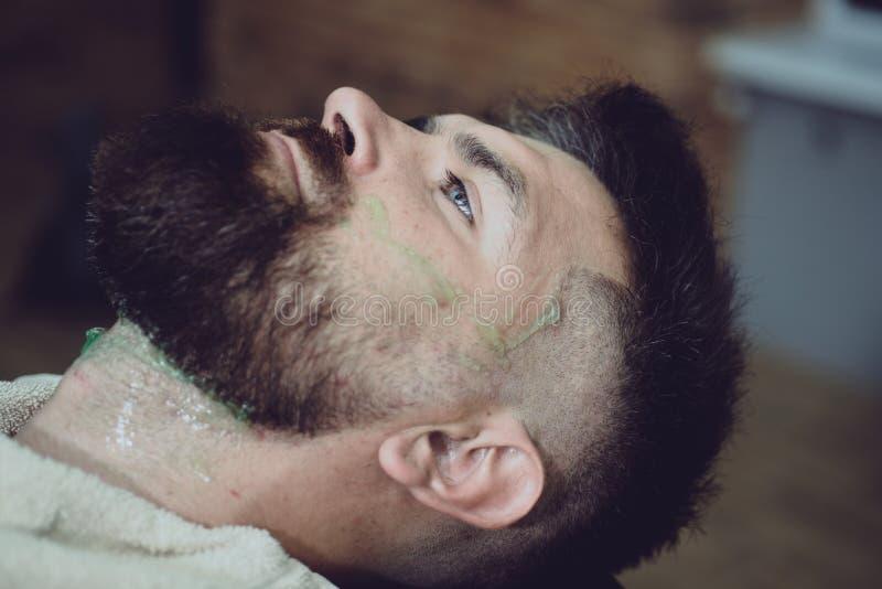 ?l est? haciendo dise?ar con la m?quina de afeitar Peluquero profesional en interior de la barber?a Estilista y peluquero var?n imagenes de archivo