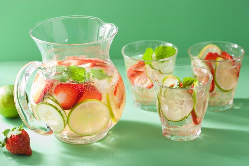 L'estate di rinfresco beve con la calce del cetriolo della fragola in barattolo e immagine stock