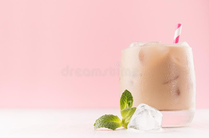 L'estate ha ghiacciato il cocktail alcolico del caffè con i cubetti di ghiaccio, la menta verde, la paglia a strisce sulla paret fotografia stock