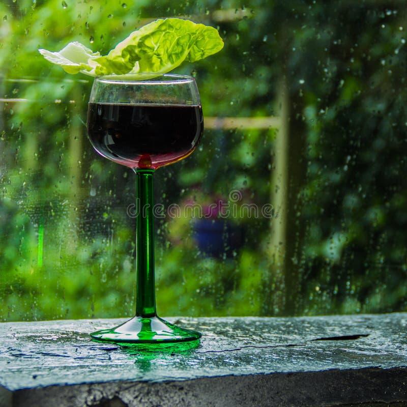 L'estate sta venendo, pioggia nel giardino, vetro di vino rosso su w fotografia stock libera da diritti