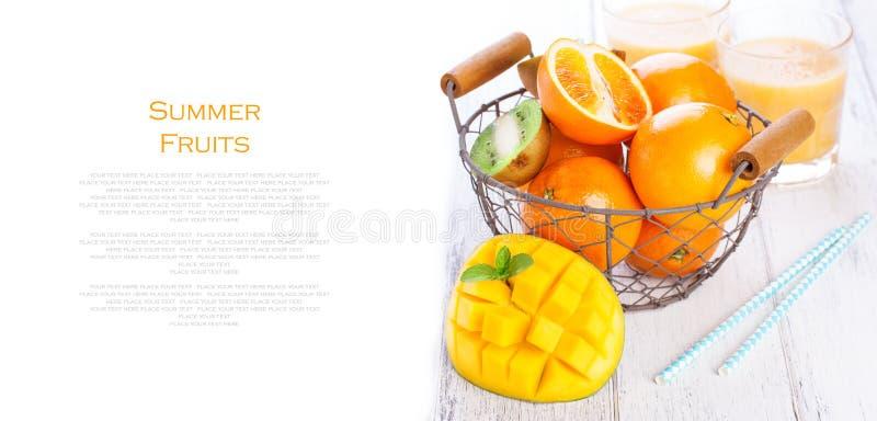 L'estate succosa fresca fruttifica, arance, il mango, kiwi in un canestro d'annata ed il rinfresco beve su una tavola di legno fotografia stock