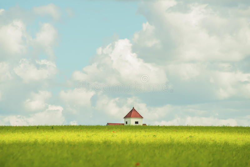 L'estensione dei campi e del tetto di una casa sola nella distanza fotografia stock