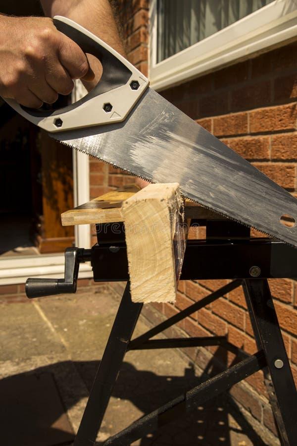 L'esterno di legno di sawing dell'uomo facendo uso di una mano ha visto fotografie stock