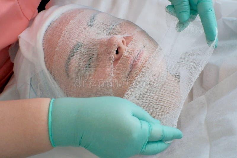 L'estetista copre il fronte della donna della garza per la maschera dell'alginato Il fronte della donna e estetista delle mani in immagine stock libera da diritti