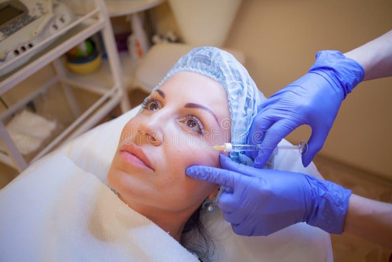 L'estetista di medico aumenta il paziente del labbro una stazione termale della siringa dell'iniezione fotografia stock