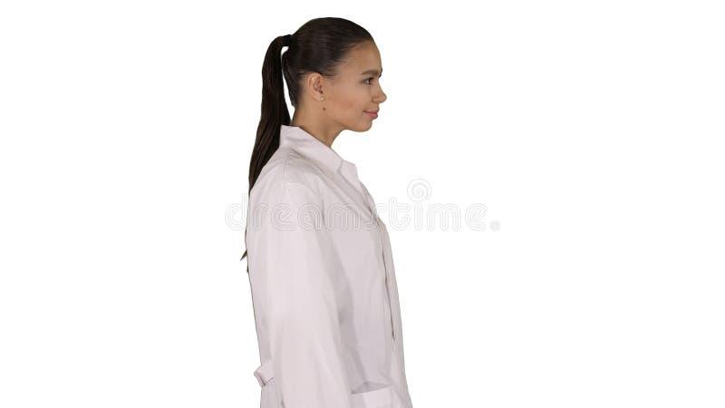 L'estetista di medico in un abito bianco sta camminando su fondo bianco immagine stock