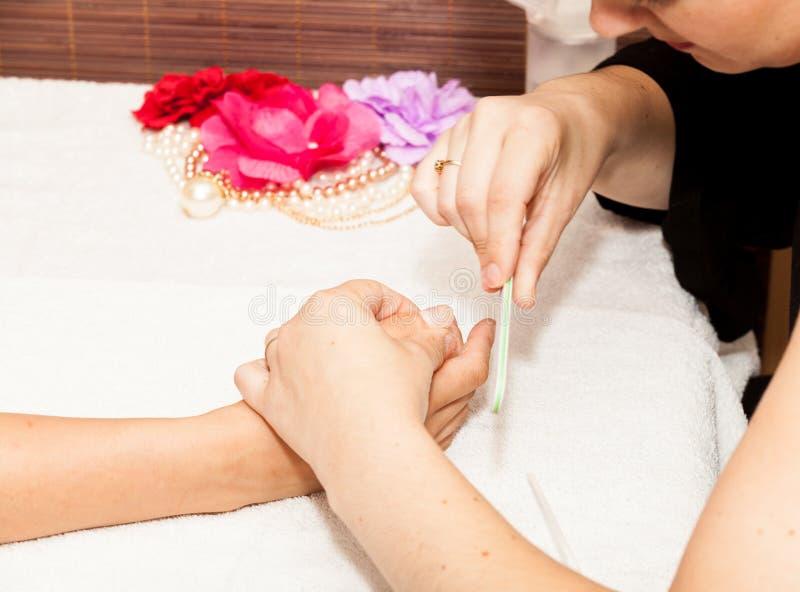 L'estetista lucida i chiodi del cliente prima di mettere smalto per unghie fotografie stock libere da diritti