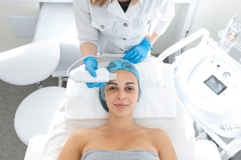 L'estetista pulisce la pelle del paziente con uno scrubber a ultrasuoni Una ragazza sta subendo un ciclo di cure termali durante  fotografie stock libere da diritti