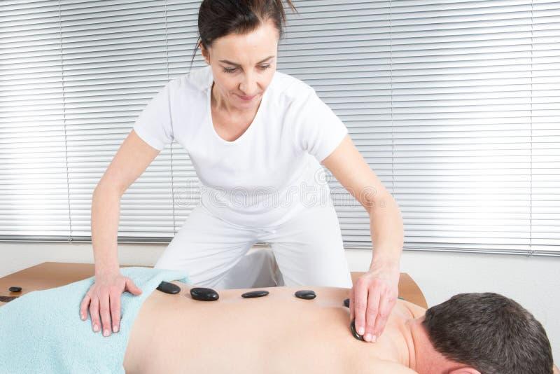 L'esthéticien de masseuse exécute un traitement avec les pierres noires images libres de droits