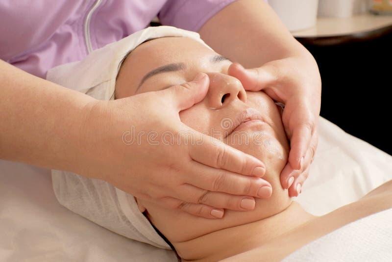 L'esthéticien en gros plan applique la crème hydratante sur le visage de la fille après la procédure Traitements dans le salon de photos libres de droits