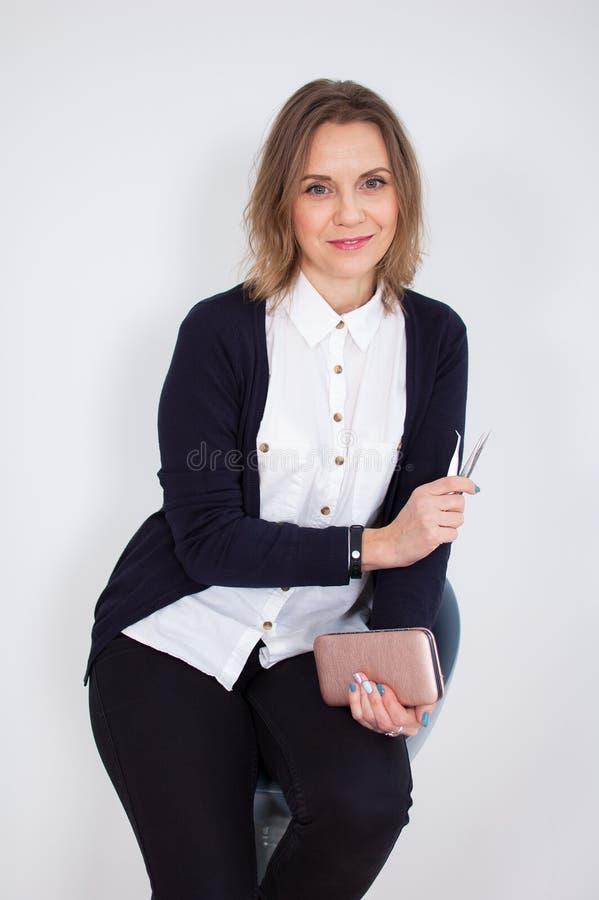 L'esthéticien féminin assez bel dans la chemise et le pantalon noir tient des instruments pour des traitements de beauté sur ses  photographie stock