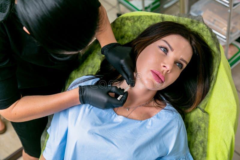L'esthéticien injecte les injections botulinum de toxine dans le cou de la femme Femme de Moyen Âge sur des procédures cosmetolog photos libres de droits