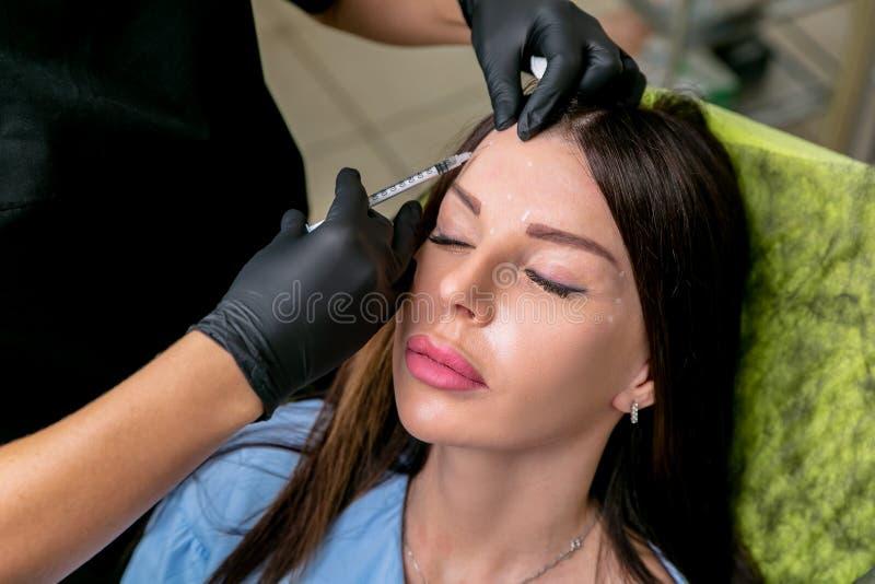 L'esthéticien injecte les injections botulinum de toxine dans le front de la femme Femme de Moyen Âge sur des procédures cosmetol photographie stock libre de droits