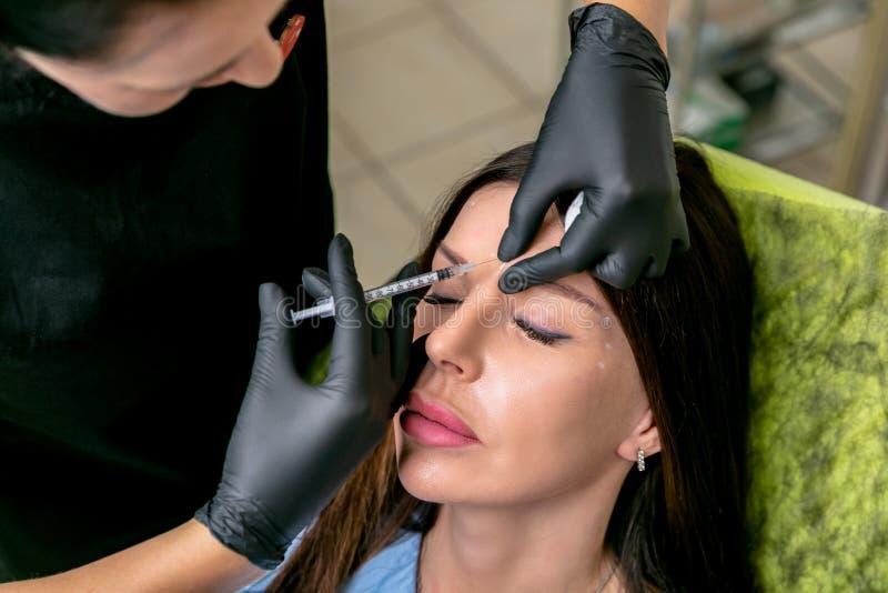 L'esthéticien injecte les injections botulinum de toxine dans le pont du nez de la femme Femme de Moyen Âge sur des procédures co images stock
