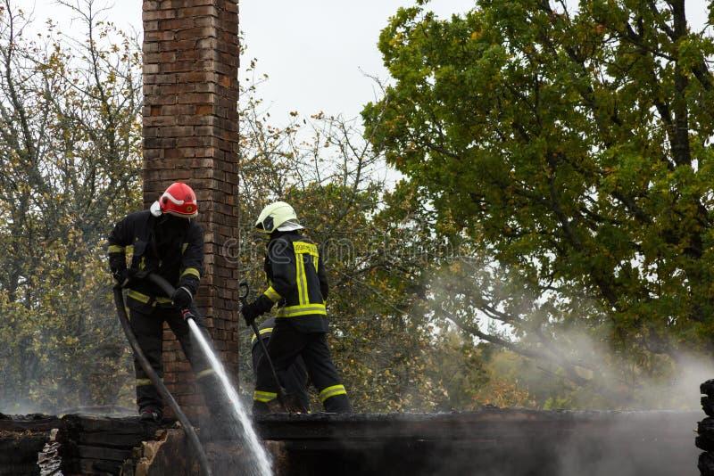 L'estinzione del fuoco ha distrutto la casa del villaggio sul quinto ottobre fotografia stock