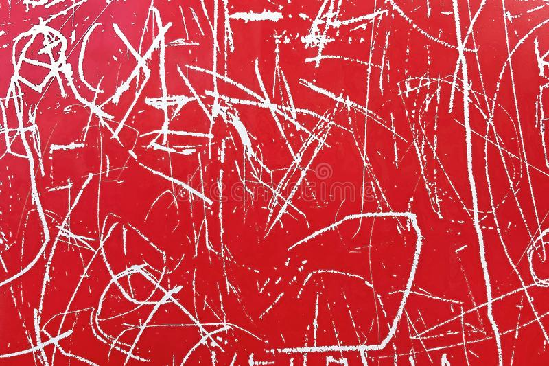 L'estratto graffia il bianco su un fondo rosso, struttura fotografia stock libera da diritti