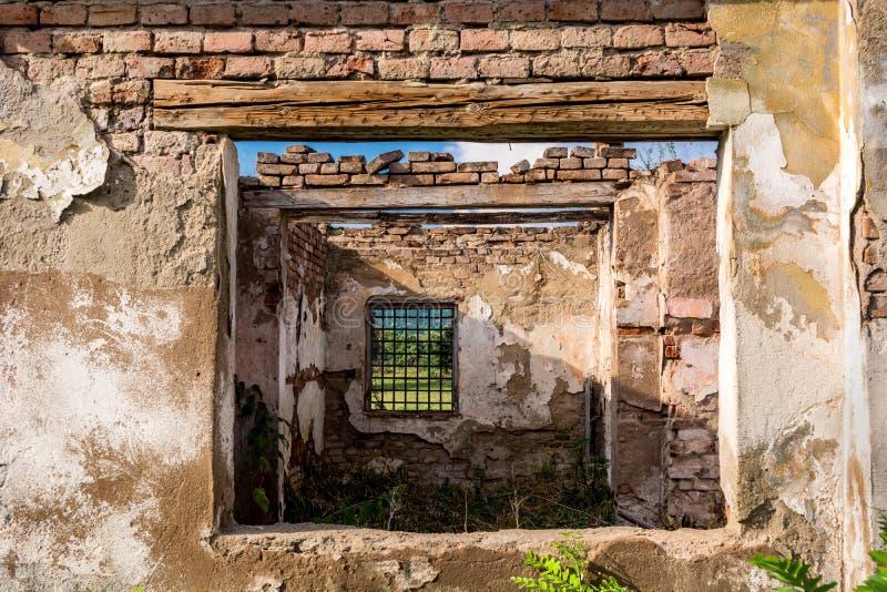 L'estratto incornicia le finestre ed interno, rovine di una costruzione rovinata abbandonata Vecchi mattoni rovinati delle pareti fotografia stock libera da diritti