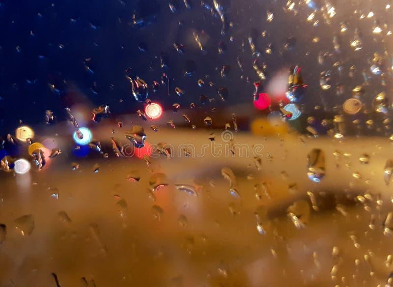 L'estratto vago del vetro di finestra bagnato con le gocce di pioggia e lo scintillio del bokeh accende il fondo il giorno piovos fotografia stock libera da diritti