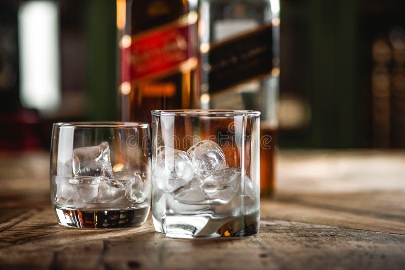 L'etichetta rossa e le bottiglie ed il vetro di whiskey neri dell'etichetta con ghiaccio figliano immagini stock