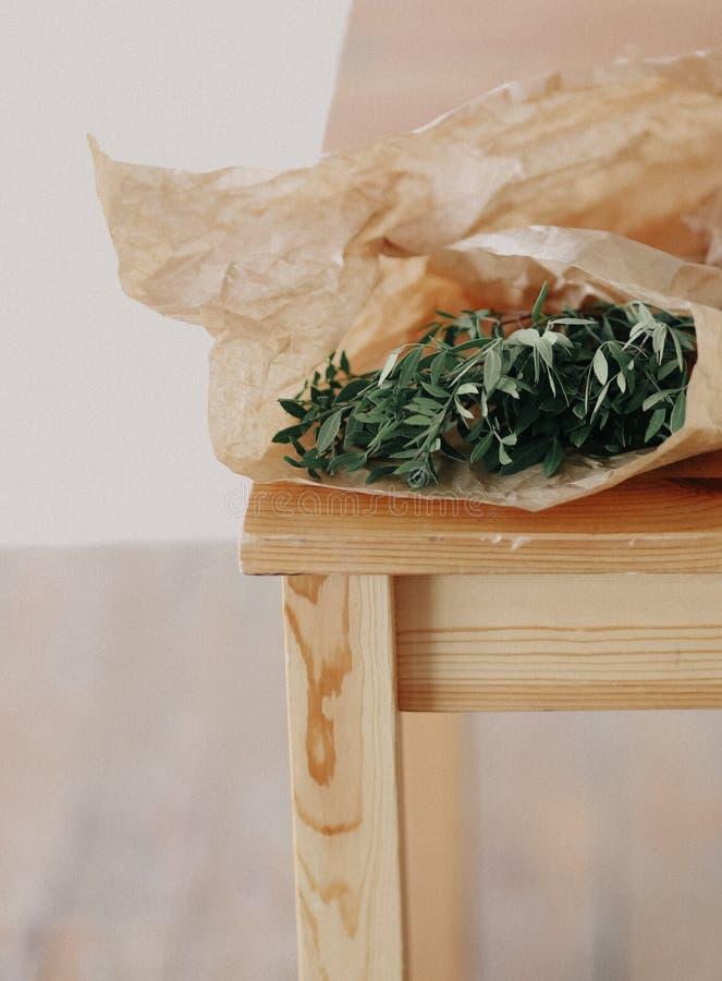 L'eucalyptus verde lascia la sedia di legno di carta decorativa avvolta fotografia stock