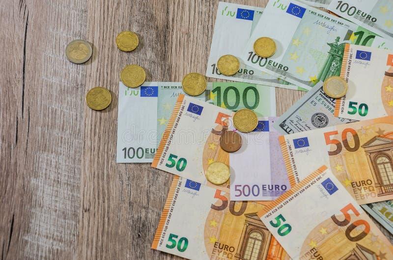 L'euro, dollars, cents a étendu sur un fond en bois image stock