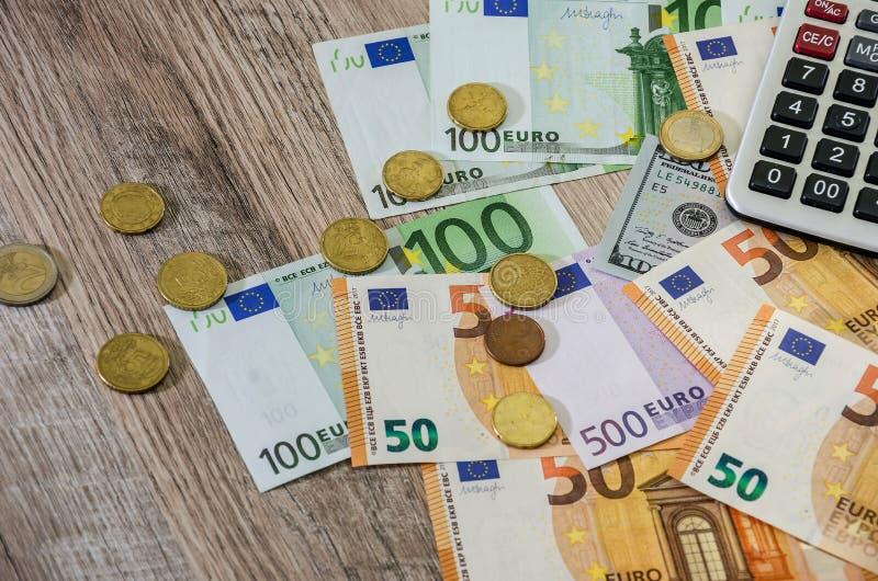 L'euro, les dollars, les cents et la calculatrice ont ?tendu sur un fond en bois image libre de droits