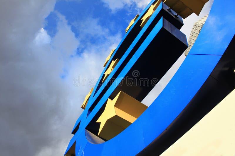 L'euro segno alla banca centrale europea acquartiera a Francoforte, Germania con le nuvole drammatiche scure che simbolizzano una immagini stock
