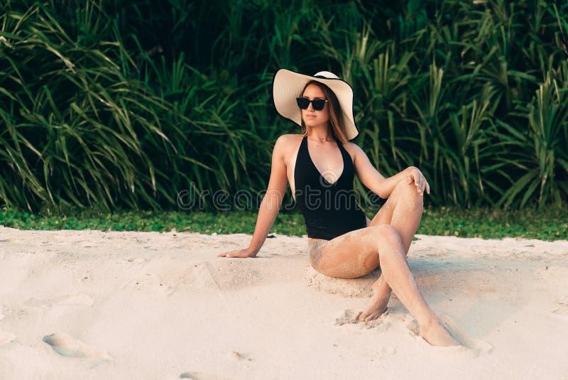 L'europeo con pelle liscia molle riposa sulla spiaggia, prendente il sole e godendo del sole, porta un costume da bagno nero alla immagine stock libera da diritti